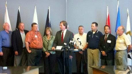 Mayor Bartlett, flanked by other elected and appointed officials, announces the lawsuit.
