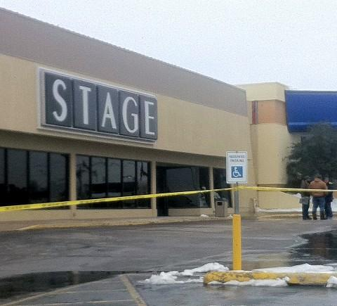 With the parking lot blocked-off, workers survey the damage at the Broken Arrow Stage store.