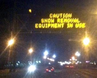 Sign over Highway 169 warns motorists of snow plows ahead.