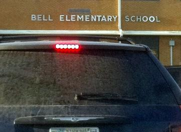 A car stops in front of Bell Elementary so that the driver can sign a petition.