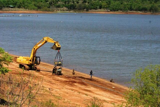 Heavy equipment is moved into a place to help fish a crane from Kaw Lake.
