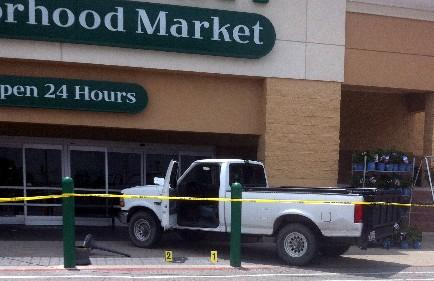 Placards mark the shell casings outside a crashed pick-up at the 21st and Yale Wal-Mart grocery store.