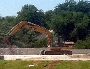 Heavy equipment is bringing down the old bridge.