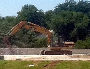 Heavy equipment is bringing down the old bridge.