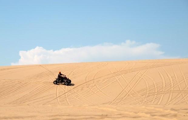 A man rides an ATV across the sand at Beaver Dunes, a former state park recently acquired by the City of Beaver.