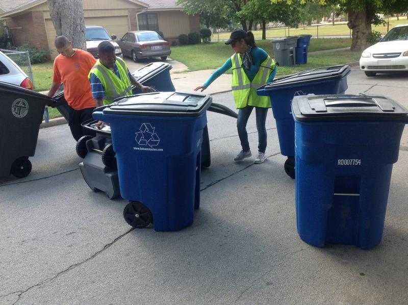 Crews deliver new trash and recycling carts.