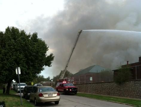 A Fire Department snorkel truck hoses down the building's roof.