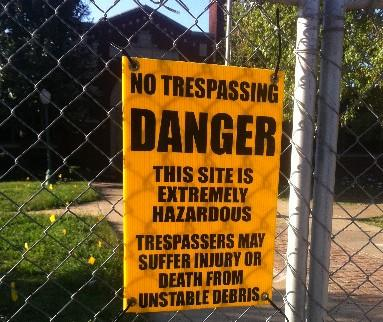 The No Trespassing sign on the chain-length fence outside of the remains of the Barnard School.
