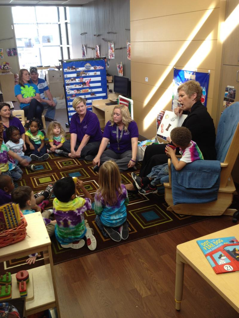 A teacher reads to a group of students.