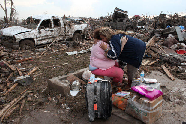 Stella Howard hugs her daughter Dawnelaina amid the remains of Stella's Moore home.