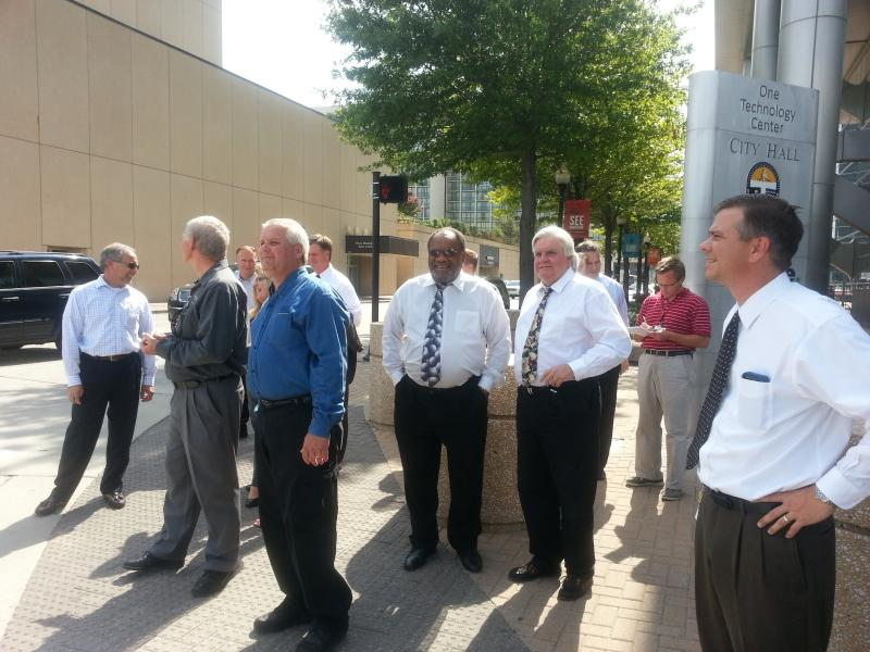 Representatives of Public Service Company of Oklahoma and City of Tulsa officials wait to cross Cincinnati Avenue Thursday on their way to a presentation on moving city utility lines underground.