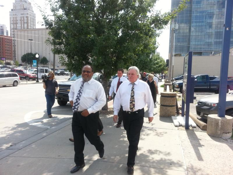 Councilors Jack Henderson (left) and Byron Steele walk eastbound on Second Street toward PSO's presentation on underground lines.