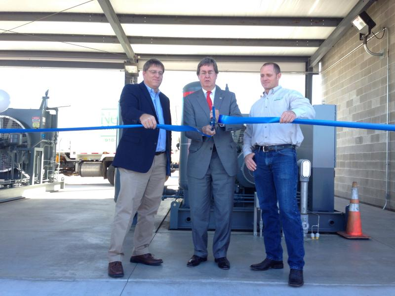 Blue Energy Fuels President Tom Sewell (left) and NeWSolutions President Jason Kannady (right) hold the ribbon Monday for Mayor Dewey Bartlett to cut at the companies' CNG fueling station dedication.