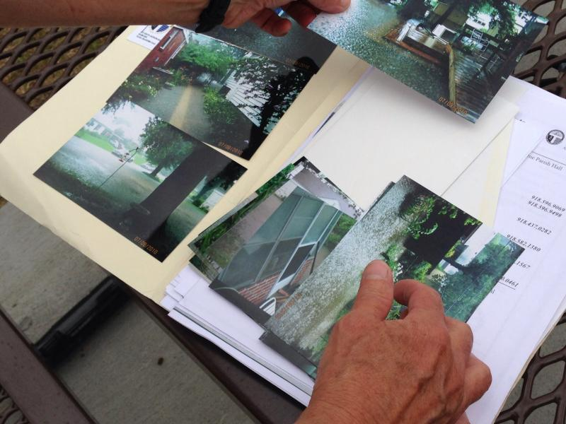 Florence Park South resident Patricia Seibert shows photos of various years' floods. She began working with the city to mitigate the flooding in 2007.