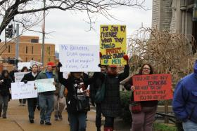 Protestors march during SLU's board of trustees meeting