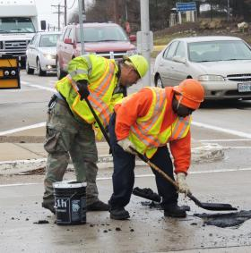 Missouri Department of Transportation workers patch a pothole on Monday on South Woods Mill Road near Route 40 in Town and Country.