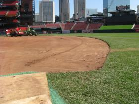 Groundskeepers work to scour about an inch and a half of dirt from the basepaths.