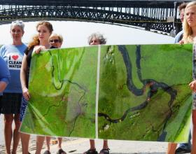 Environmental activists hold a map showing why they oppose putting hazardous waste in floodplains. The image on the right shows the reach of the Flood of 1993.