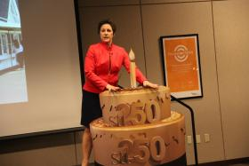 Executive Director of stl250, Erin Budde, stands next to an example of an ornamental birthday cake.