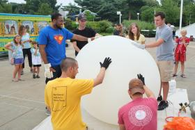 SLU students Joseph Wilkins, Patrick Walsh, Jackie Ringhausen and Tim Barbeau (standing, from left to right), and Valparaiso Univ. trainers Alex Kotsakis and Mark Spychala (crouching, left to right) stabilize the balloon as it fills with helium.