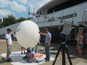 A large antenna captures the ozone and weather data and sends them to a radio receiver. In the background, SLU students Patrick Walsh (left) and Jackie Ringhausen (seated), and Valparaiso student Mark Spychala (right) prepare the balloon for launch.