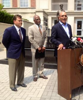 Reverend Dr. Freddy J Clark, at podium and businessman David R. Spence are filling the spots created by the resignation of Floyd C. Warmann and Gregory Sansone. St. Louis County Executive Charlie Dooley stands in center.