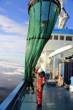 A crew member aboard the Norwegian Polar Institute's research ship, R/V Lance, prepares to deploy a huge seine net used for collecting phytoplankton and zooplankton from continuous water columns over 1000 feet deep along the continental shelf off the coast of Spitsbergen Island in the Svalbard archipelago.