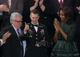 Cory Remsburg, flanked by his father, Craig, and First Lady Michelle Obama, responds to the ovation Tuesday night.