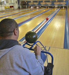 Veteran Scott Richards of St. Louis, an outpatient, bowls using a portable ramp.