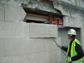 Workers remove the cornerstone of the old Jewish Hospital to place it in storage. It will be incorporated into the new building.