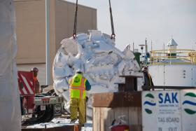 Workers prepare to lower the cutterhead of the Tunnel Boring Machine into the starter tunnel shaft.
