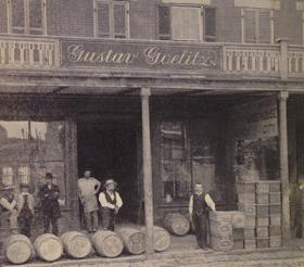 Gustav Goelitz, with his knee up on a barrel in the center, in front of his confectionery in Belleville, Illinois.