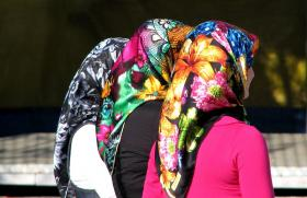 three women wearing colorful headscarves