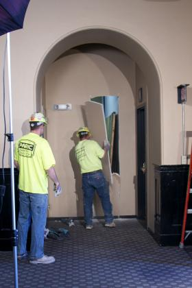 Workers cut into a wall at Union Station so long-lost mural panels could be brought out.