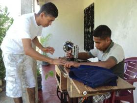 Ostin works to teach tailoring to Chemo (right).