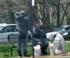 A couple with their groceries sit at a bus stop on the north side last week.