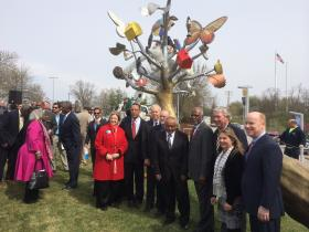 Higher education leaders, municipal and county officials, and onlookers pose in front of the statue.