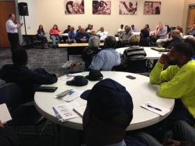 The project manager for contractor AMEC, Gene Watson, talks about the company's plans for hiring minorities to work on the Carter Carburetor cleanup. Meeting attendees ― many of them would-be workers on the project ― look on.