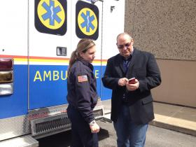 Shannon Watson, community health supervisor in the EMS; and EMS Chief Chris Ceborello reviewing EMS data on recent calls for service. in front of an EMS vehicle.