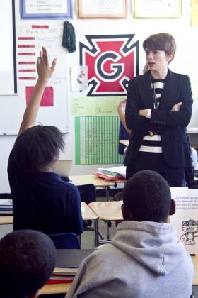 student raises hand in Michelle Oloya's class