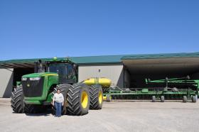 Shelley Finfrock stands in front of her tractor on her family's home farm in central Illinois. The attached planter can sow 48 rows of corn, covering an 80-foot swath of field at one time.