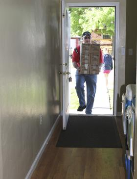 Larry Miller helps unload a food delivery for Twigs.