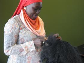 Ndioba Niang, one of two plaintiffs in a lawsuit challenging the Missouri law that forces hair braiders to have a cosmetology license, works on the hair of Leia Jackson on June 17, 2014.
