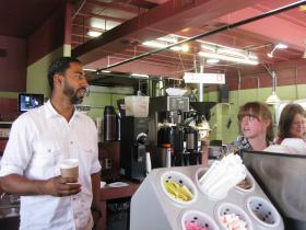 Jason Wilson, coffee in hand, talks with two of his workers at the Northwest Coffee Shop in the Central West End.