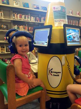 Kaiya Truesdell, 2, of Kirkwood, tries out the iPad literacy station at Kirkwood Public Library on Thursday, July 10, 2014.