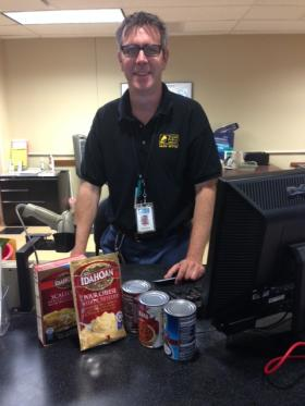 Library clerk John Copithorne accepting food in exchange for fine forgiveness at the Schlafly Branch. He said some library users hold off on paying fines until July.