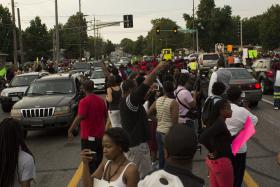Protesters line the center lane of W. Florissant Ave. on August 14, 2014. It was the first night the road was open to traffic in four nights.