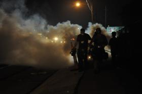 Clouds of tear gas hang over West Florissant Ave. on August 17, 2014, as police try to disperse a crowd they said had grown violent.
