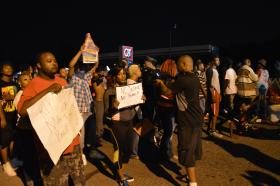 Demonstrators stand in front of the Quik Trip late Tuesday evening.