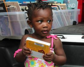 In from of the Sweet Reads van, 2 year old Lei'onna Hawthorne clutches her book about animals.